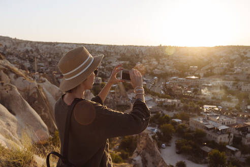 Side view of young woman photographing town with smart phone during sunset, Cappadocia, Turkey - KNTF03273