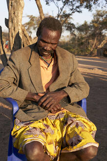 Soba of the Muhila tribe sitting on his chair, Kehamba, Chibia, Angola - VEGF00539