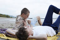 Friends relaxing on beach, daydreaming, lying on blanket - AMEF00070