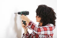 Woman using portable drill, marking with pencil on a wall - RTBF01348