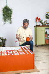Man painting furniture with brush at home - RTBF01357