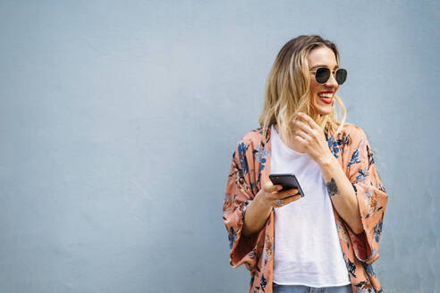 Smiling blond woman using smartphone, blue background - MPPF00015