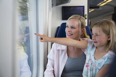 Mother and daughter traveling by train, pointing out of window - FKF03609