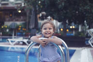 Portrait of cute little girl by the poolside - MOMF00750