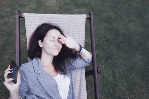 Relaxed woman with cell phone lying in deckchair in garden - KMKF01029