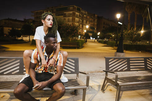Cool young couple on a bench at night in the city - LJF00784