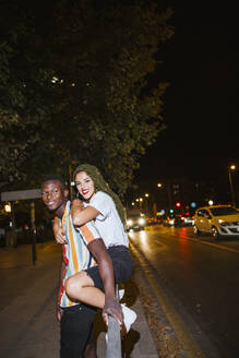 Happy young couple on the street at night in the city - LJF00787