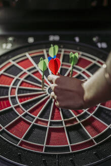 Close-up of woman's hand with darts in electronic dartboard - LJF00802