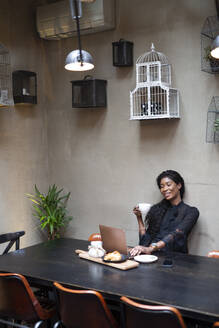 Chic businesswoman using laptop at table in a cafe - ALBF00986
