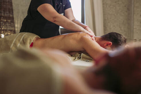 Man receiving a back massage in a spa - LJF00866