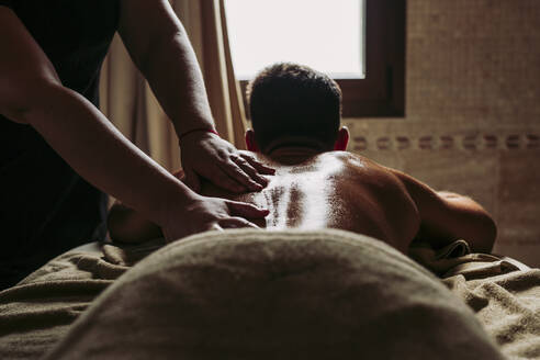 Man receiving a back massage in a spa - LJF00869