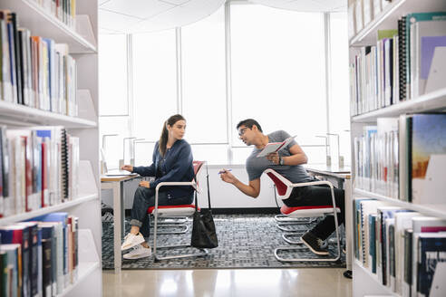 Students working at desks in univerity library and having conversation - HEROF37978