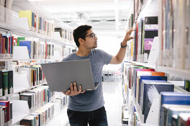 Student with laptop looking for book on shelf in library - HEROF37981