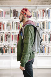 Portrait of student in university library with backpack - HEROF38023
