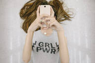 Young woman lying down with smartphone obscuring her face - HEROF38065