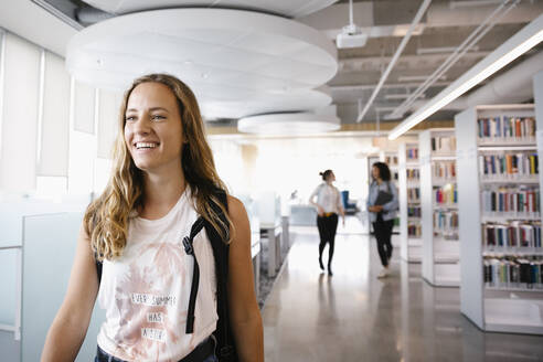 Cheerful student smiling in university library - HEROF38077