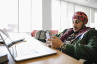 Student wearing turban smartphone in library - HEROF38134
