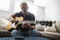 Senior man playing guitar on living room sofa - HEROF38189