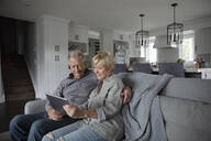 Senior couple using digital tablet on living room sofa - HEROF38243