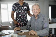 Portrait confident senior man with home healthcare nurse at dining table - HEROF38258