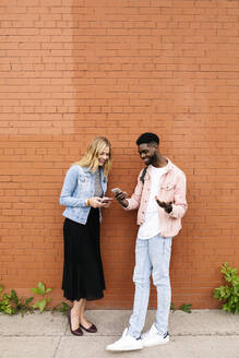 Young couple using smart phones against brick wall - HEROF38306