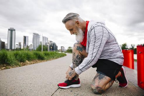 Mature male runner tying shoelace in urban park - HEROF38354