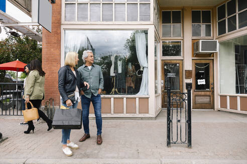 Senior couple with shopping bags outside boutique - HEROF38360