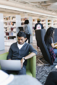 Student sitting in library and using laptop - HEROF38387