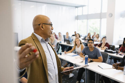Male lecturer giving presentation to university students - HEROF38444