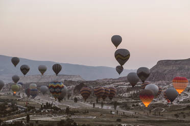 Colorful hot air balloons flying over landscape against clear sky at Goreme National Park, Cappadocia, Turkey - KNTF03274