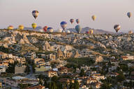 Hot air balloons flying over buildings against clear sky at Goreme National Park, Cappadocia, Turkey - KNTF03277