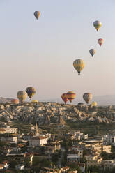 Colorful hot air balloons flying over buildings against clear sky at Goreme National Park, Cappadocia, Turkey - KNTF03280