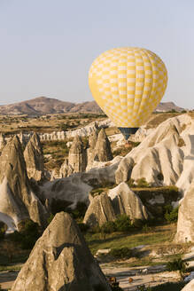 Yellow hot air balloon flying over land against clear sky at Goreme National Park, Cappadocia, Turkey - KNTF03283