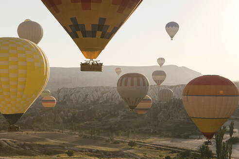 Multi colored hot air balloons flying over mountains at Goreme National Park during sunset, Cappadocia, Turkey - KNTF03286