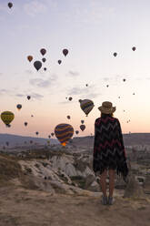 Young woman and hot air balloons in the evening, Goreme, Cappadocia, Turkey - KNTF03296