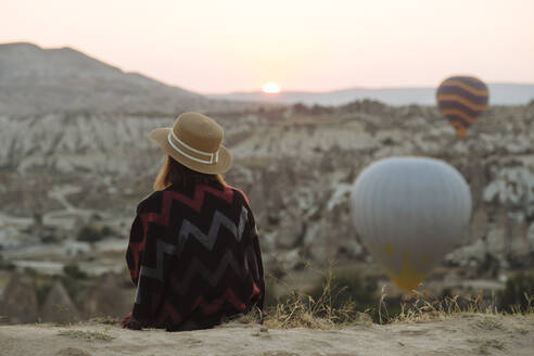 Young woman and hot air balloons in the evening, Goreme, Cappadocia, Turkey - KNTF03299