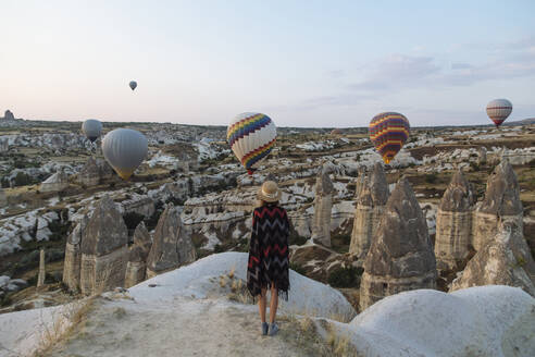 Young woman and hot air balloons in the evening, Goreme, Cappadocia, Turkey - KNTF03302