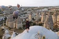 Young woman and hot air balloons in the evening, Goreme, Cappadocia, Turkey - KNTF03305