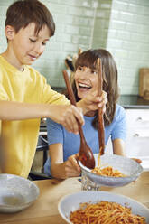 Mother eating spaghetti with her son in the kitchen - MCF00165