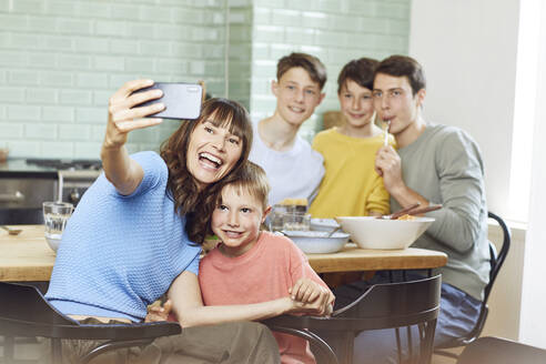 Mother and her four sons taking smartphone selfies at lunch - MCF00171