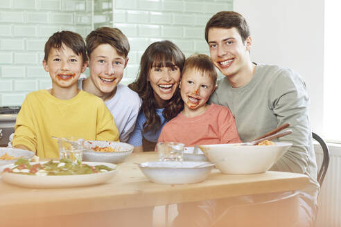 Portrait of mother and sons at lunch, with faces full of tomato sauce - MCF00174