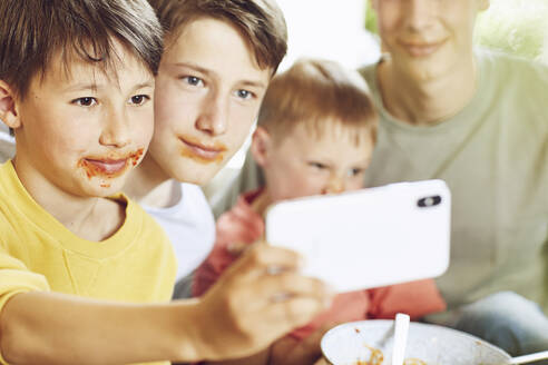 Four brothers taking selfie with faces full of tomato sauce - MCF00177