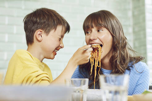 Son feeding mother with spaghetti in the kitchen - MCF00186