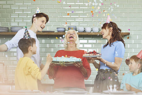 Mother and sons celebrating grandmother's bithday in their kitchen - MCF00204