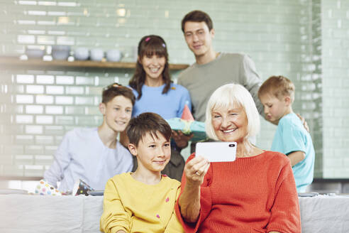 Mother and sons celebrating grandmother's bithday in their kitchen, boy taking selfies - MCF00213