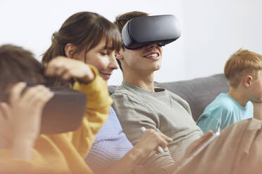 Happy family sitting on couch, using VR goggles and mobile devices - MCF00225