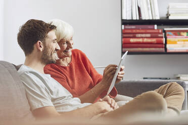 Grandson sitting on couch, using digital tablet with his grandmother - MCF00252