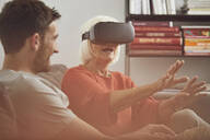 Grandmother using VR glasses with her grandson - MCF00258