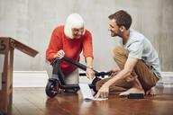 Grandson explaining e-scooter to his grandmother - MCF00261