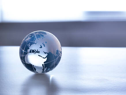 Global Markets, A glass globe illustrating the world on a desk. - ABRF00434